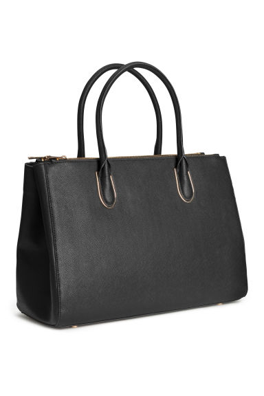 Spacious handbag in thick, grained faux leather with two handles and a zip at top. Three inner compartments, one with zip. Studs at base. Lined.