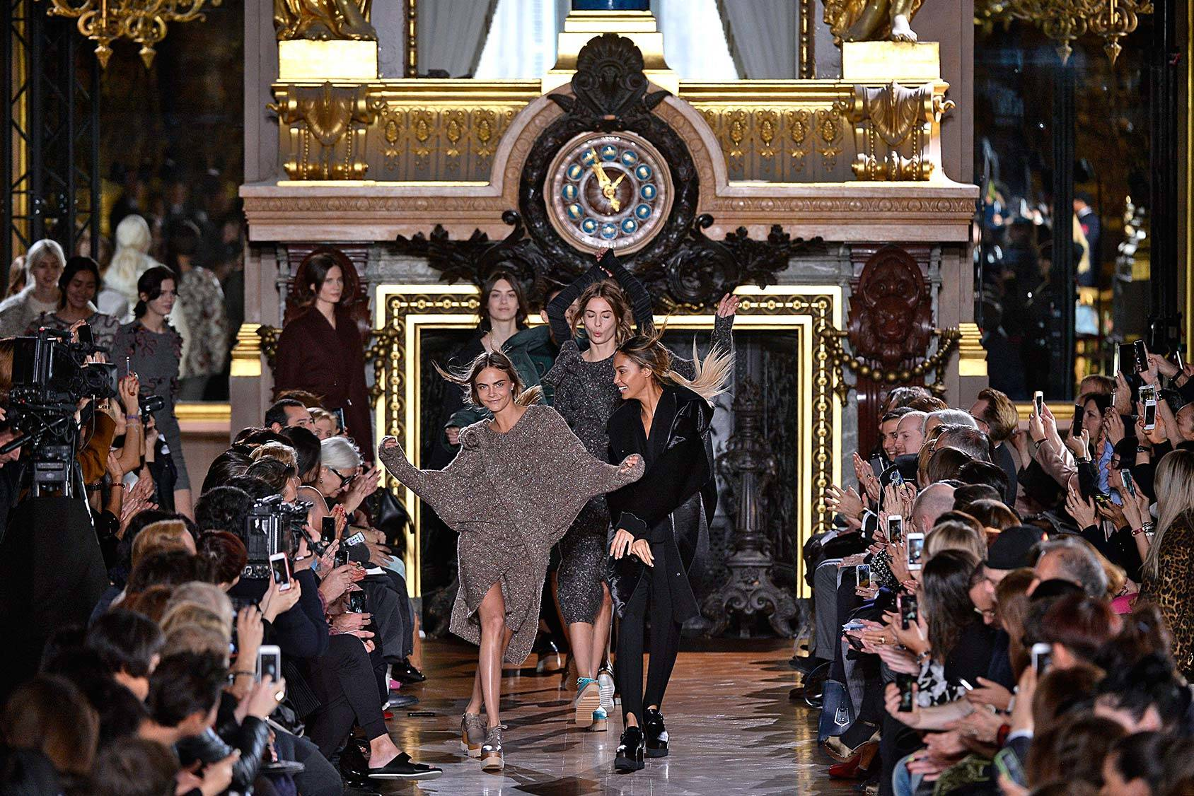 Cara Delevingne and Joan Smalls dance their way down the catwalk at the Stella McCartney Fall/Winter 2014 fashion show, All Over Press.