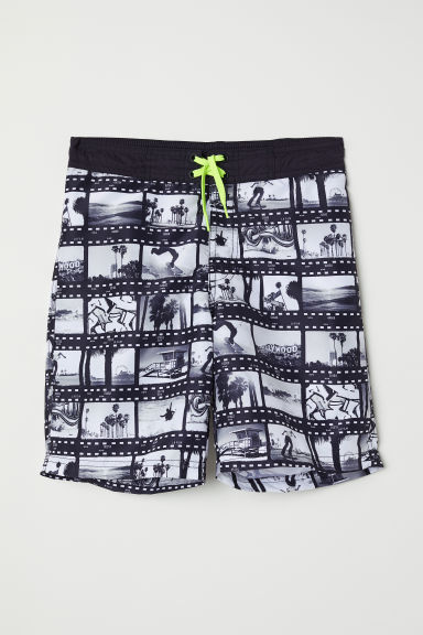 Printed swim shorts - Black/Film reel - Kids | H&M GB