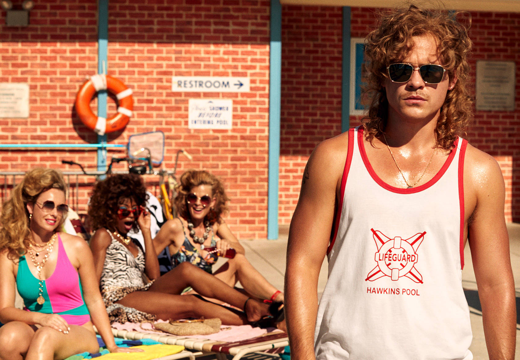 H&M Guy wearing a white lifeguard vest standing and sunglasses with three girls behind him on sun loungers - STRANGER THINGS