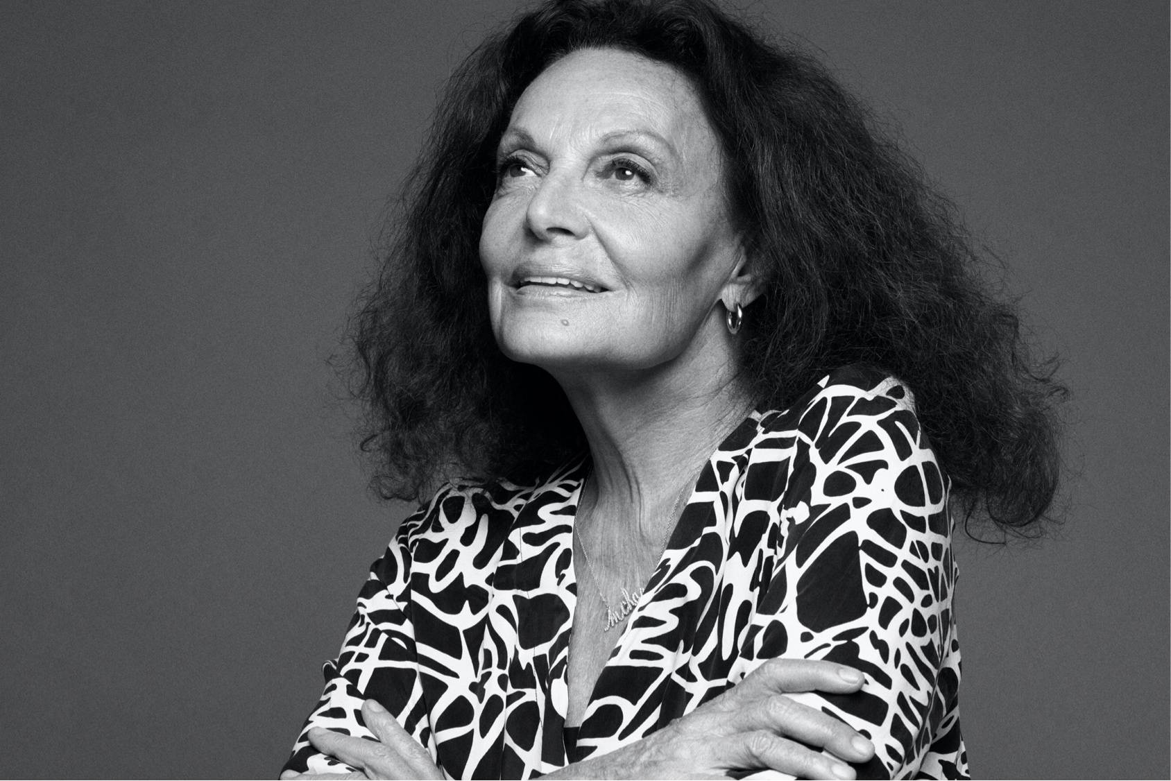 B&W portrait of Diane Von Furstenberg in a black and white blouse, smiling and looking up.