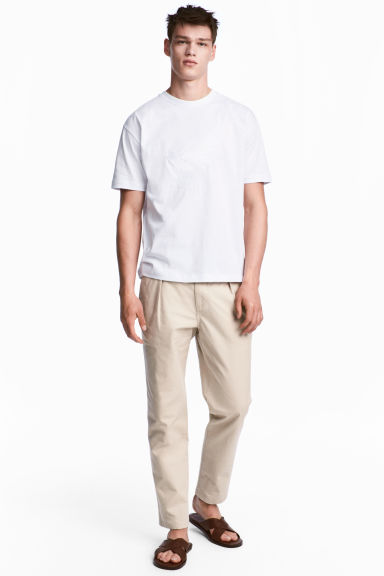 Pleat-front chinos Relaxed fit - Light beige - Men | H&M